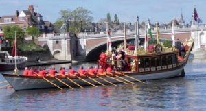 The Queen stands on a long barge with 20 rowers rowing along the River Thames