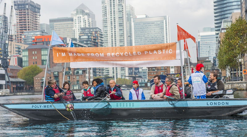 group of people in a boat with a sign that says I'm Made of Recycled Plastic