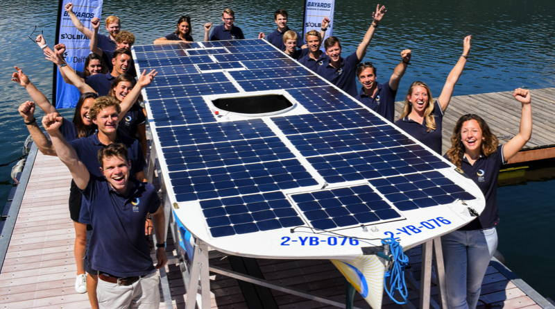 The students of the solar boat team hold up their boat and raise their arms for the camera