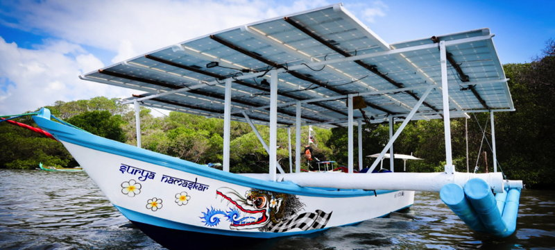 A brightly painted Indonesian outrigger boat with a solar panel roof