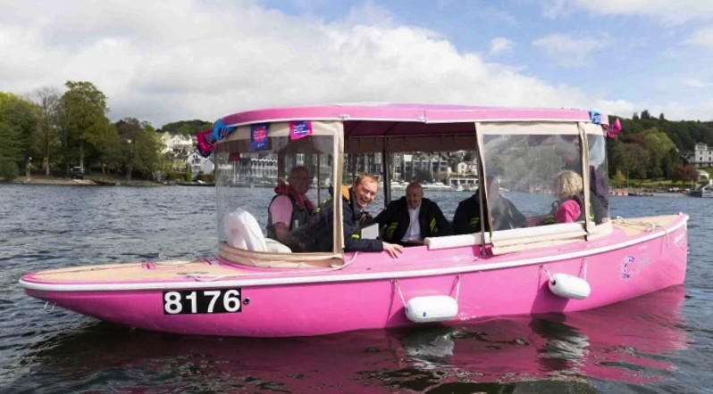 A pink electric boat with people inside enjoying the cruise