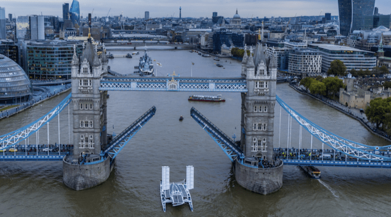 the Energy Observer zero emission ship sails under the raised drawbridge of London's Tower Bridge