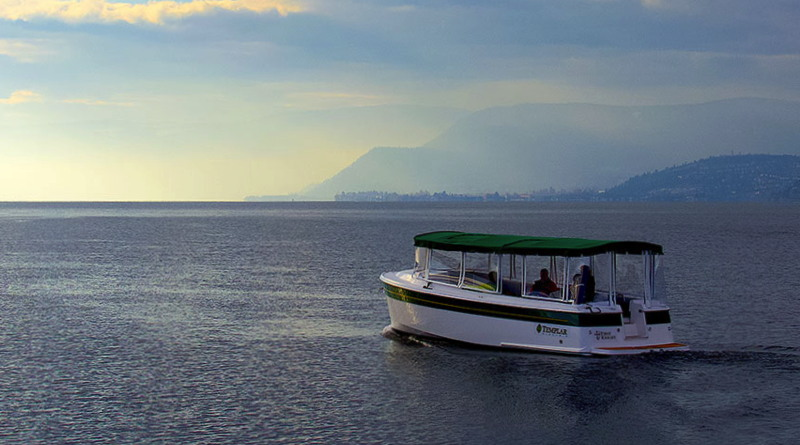electric motor optimizers will go in boats like this electric boat cruising along at sunset on a lake with mountains
