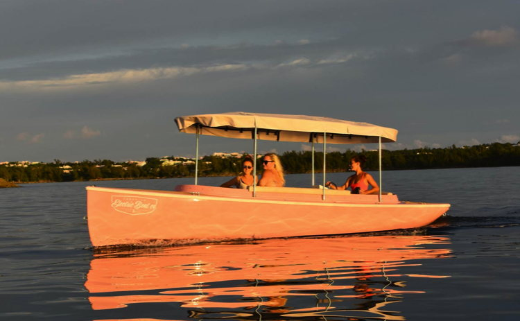 People in an Electric boat at sunset in Bermuda