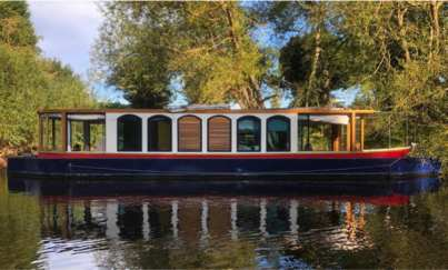 new electric narrowboat on canal with willow tree overhanging
