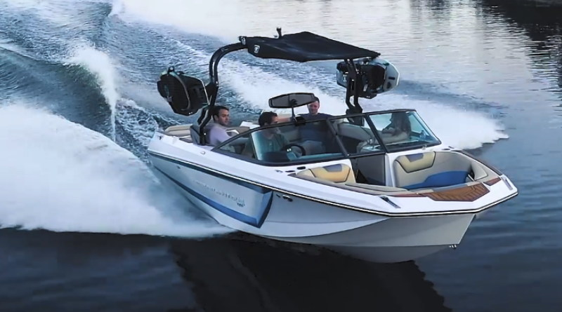 Nautique all-electric ski boat speeding along a lake with a wakeboarder in tow