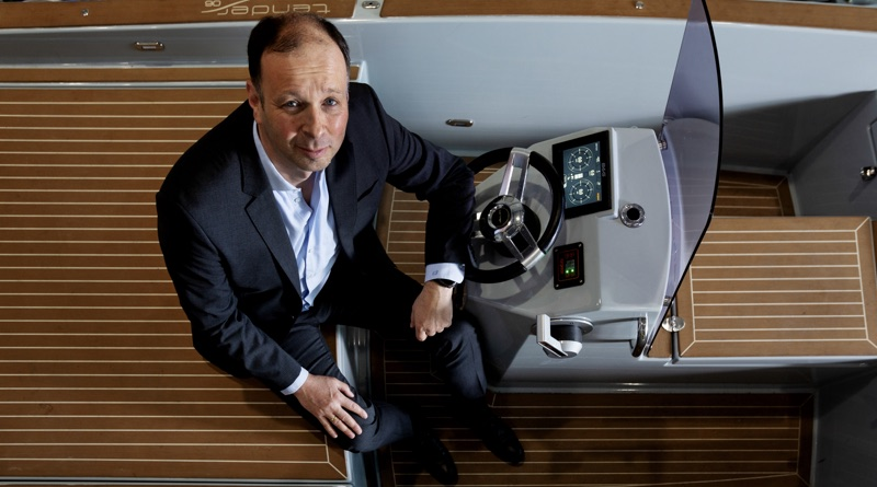 Torqeedo founder Christopher Ballin in the cockpit of a boat with controls for electric motors
