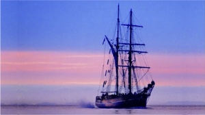 electric boat milestones - Zebu tall ship with sails down at sunset