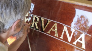 Gold leaf hand lettering being applied to a Budsin Electric Boats transom