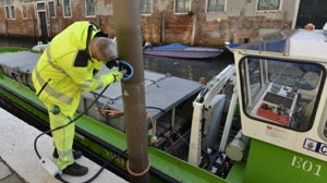electric boat charging pole in Venice being used by a city worker charging a garbage boat