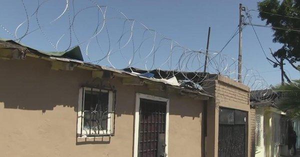 Casas protegidas con alambre de púas del muro fronterizo