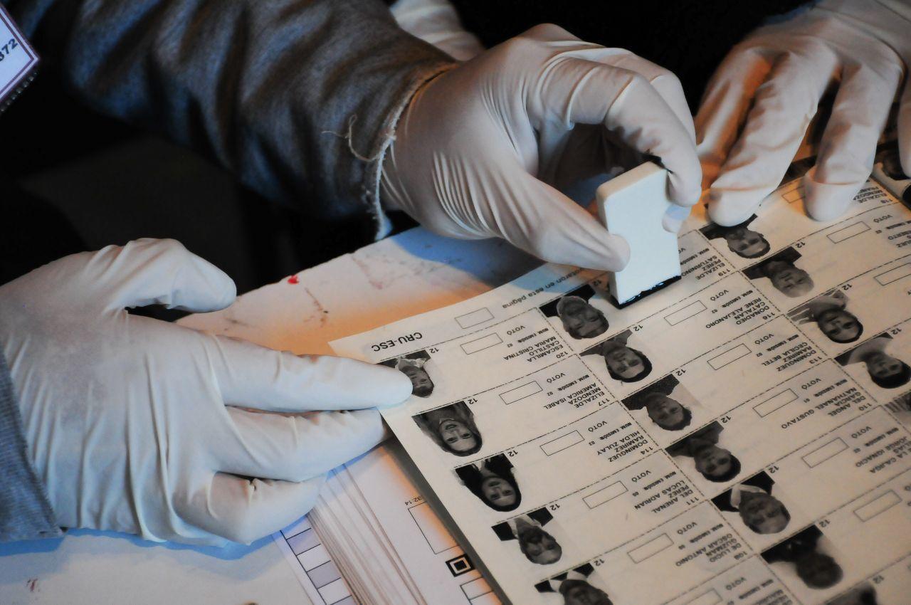 Funcionaria de casilla utiliza guantes para evitar tocar a los votantes, esto como medida sanitaria.