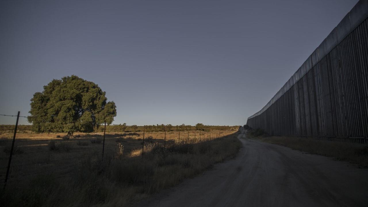 sujeto escala muro fronterizo con niña en la espalda y la abandona