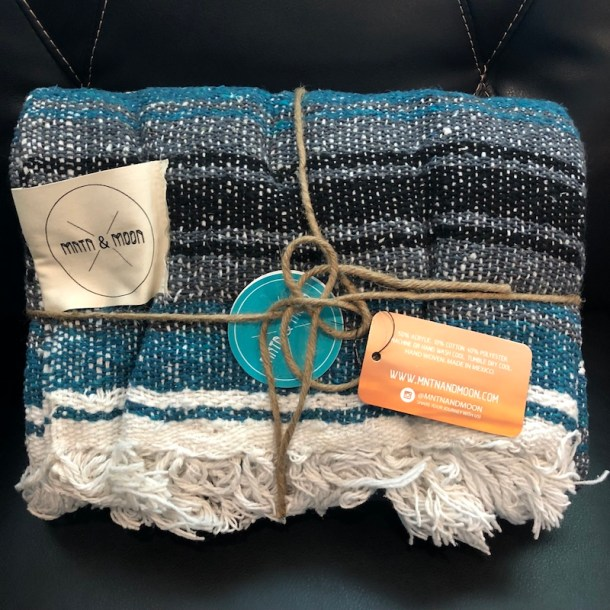 "The MNTN & MOON Lago Mexican Falsa Blanket came wrapped in reusable twine and measures 48"" wide x 73"" long. Made of 50% acrylic, 10% cotton, and 40% polyester, it's very soft. The blankets are handwoven by artisans in Mexico and hand finished in the United States."