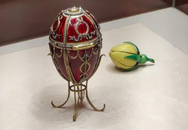 L'œuf à la rose recouvert d'émail rouge, orné de flèches de Cupidon symbolisant l'amour que porte le tsar à son épouse. Il s'ouvre pour révéler un bouton de rose jaune articulé contenant deux surprises aujourd'hui perdues : une réplique miniature de la couronne impériale et un pendentif de rubis.