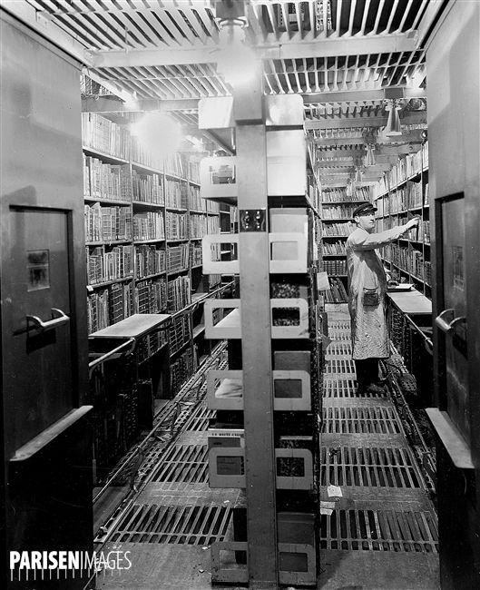 Bibliothèque Nationale. Magasin central du département des Imprimés. Recherche des livres dans une travée. Paris, 1938.