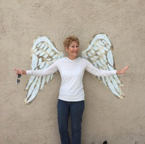 Judy Reeves in jeans and white long-sleeved blouse, standing in front of all wall so it looks like she has white angel wings