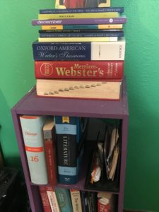 Small purple bookshelf with reference books and literary magazines stacked on it