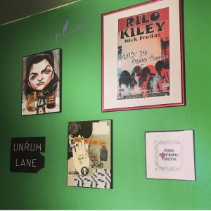 Green wall decorated with framed collages and posters.