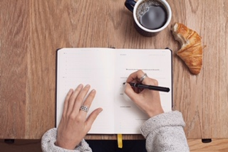 Hands of a woman in a thick beige sweater, wearing silver rings, drinking coffee, eating a croissant, and writing in a notebook with a pen