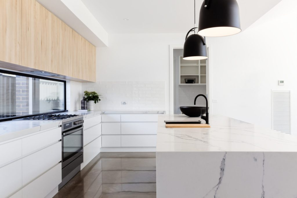 white kitchen with marble centre island and black pendant lights