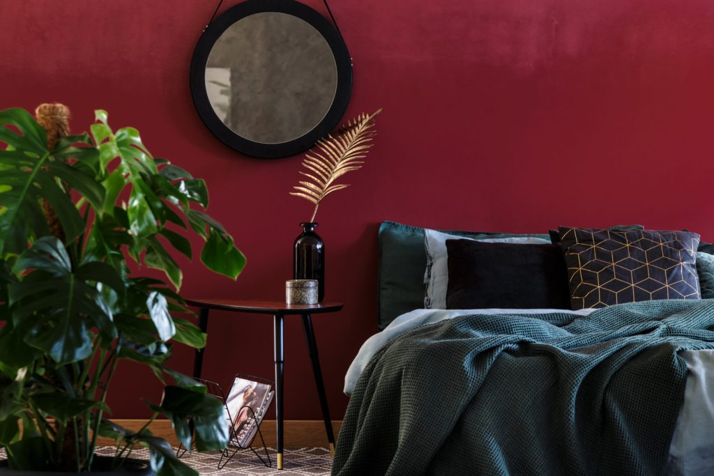 bedroom with ruby red wall and green bedding