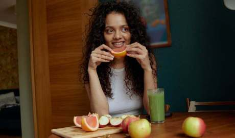 smiling woman holding sliced pomelo