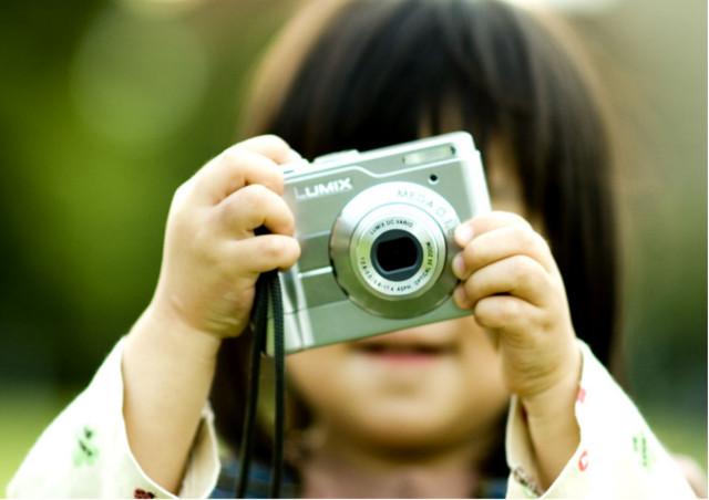 お宮参りなど子どもの成長は記念に残しておくのがおすすめ。両手にカメラを持って、ファインダーを覗いている小さなお子様の画像