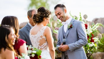 Groom laughing with his bride during their wedding ceremony at Troon North by Scottsdale wedding photographer PMA Photography.