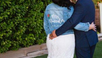 """Bride and groom showing off brides custom """"Mrs"""" denim jacket by Arizona wedding photographer PMA Photography."""