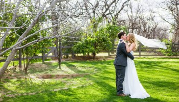 Bride and Groom share a kiss during their Venue At The Grove wedding by Arizona wedding photographer PMA Photography.