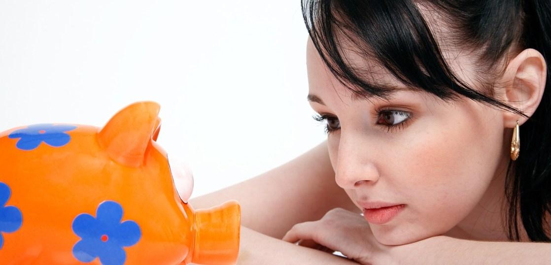 貯金箱を見つめる女性