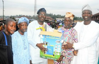Chairman Osun House of Assembly Committee on Information and Strategy, Honourable Olatunbosun Oyintiloye (3rd right); Owalare of Ilare-Ijesa, Oba Emmanuel Otebolaku (2nd right) presenting a plasma television with DSTV decoder to the Chairman, Iketewi Youths Forum, Sule Raimi, during Oyintiloye's ward to ward Empowerment programme for farmers, widows and others, at Ilare Ward 10 of Obokun East Local Council Development Area (LCDA) of Osun…during the week…