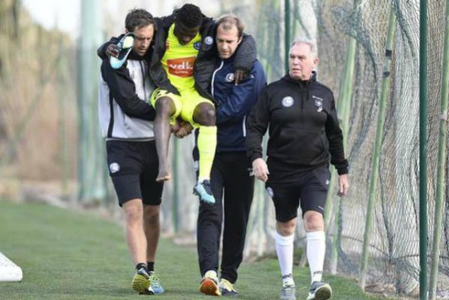 Moses Simon being helped out after his injury...