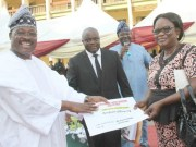 Governor Abiola Ajimobi of Oyo State (left) presenting Certificate of Occupancy under the state Home Owners Charter to one of the beneficiaries of the scheme, Mrs..Olotu Olusoji (right). With them are the State Commissioner for Lands, Housing and Survey, Mr. Isaac Omodewu (second left) and his counterpart in the Information, Culture and Tourism ministry, Mr. Toye Arulogun (second right).