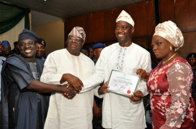 L-R: Oyo Resident Electoral Commissioner, Barr Mutiu Agboke, INEC National chairman in charge Oyo, Osun and Ekiti, Chief Solomon Adedeji presenting certificate of return to Oyo State's Governor-elect, Engr Seyi Makinde while his wife Omini looks on…