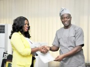Engr Seyi Makinde (right) presenting the Certificate of Occupancy to the Sales representative of the Nigeria National Petroleum Cooperation (NNPC) Retail Limited in Oyo State, Mrs Toluwase Adesanya…on Monday…