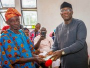 Ekiti State Governor, Dr Kayode Fayemi presenting a cheque to a retiree, Mr. Olowofela Francis…at the event…