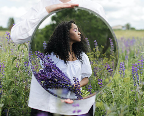 woman in a field with a mirror showing her reflection