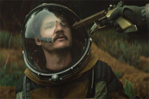 Pedro Pascal em uma roupa de astronauta com uma arma apontada para sua cabeça