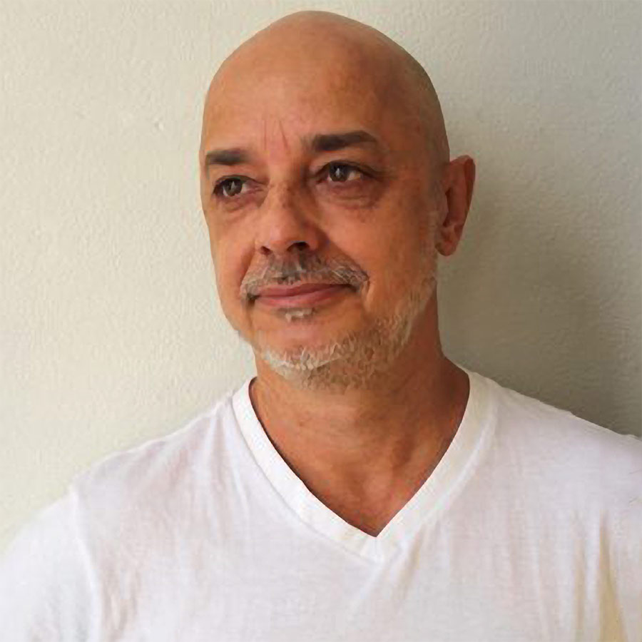 Heed and shoulders photo of Rogerio in a white T shirt against a beige wall