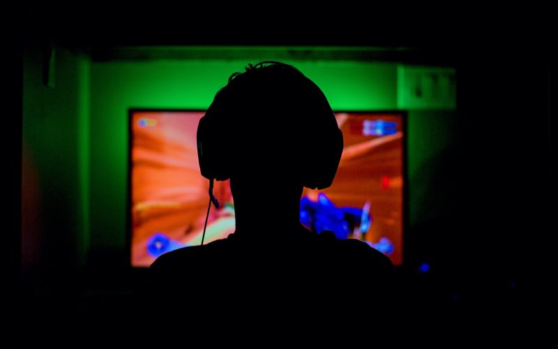 Silhouette of gamer against a tv screenwith a computer game