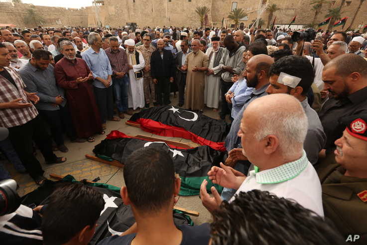 FILE - Mourners pray for fighters killed in airstrikes by warplanes of General Khalifa Haftar's forces, in Tripoli, Libya, April 24, 2019.