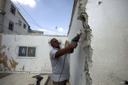In this Monday, Sept. 9, 2019 photo, Palestinian Jamil Masalmeh uses a power tool to destroy an apartment he had added to his home years earlier, in the Silwan neighborhood of east Jerusalem. When he failed to secure a permit, Israeli municipal…