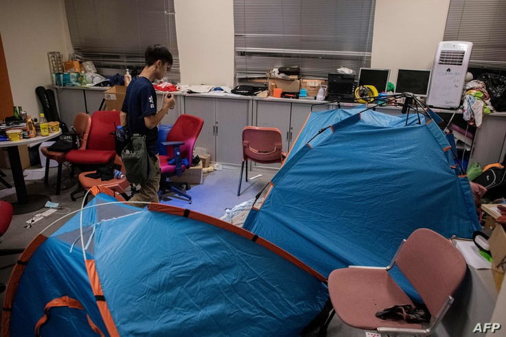 A volunteer medic searches for protesters inside of a building in the campus of the Hong Kong Polytechnic University where…