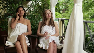 stock-footage-happy-female-friends-talking-on-cellphone-in-spa-steadicam-shot
