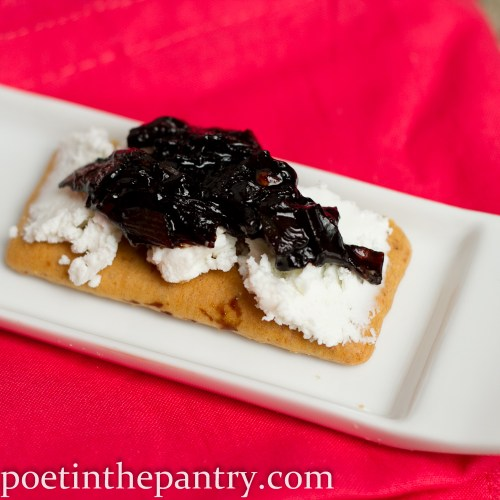 Onion jam atop goat cheese on a wheat cracker