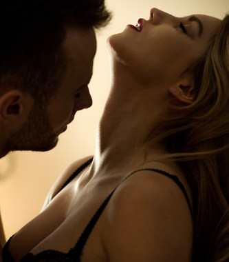 Sexy couple during foreplay, woman with head tilted back.