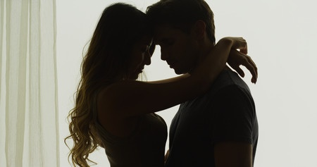 Silhouette of couple holding each other in front of window.