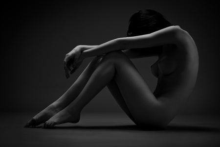 Darkened silhouette image of woman sitting naked in the dark
